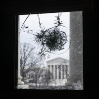 The U.S. Supreme Court, seen through a broken window at the U.S. Capitol in Washington on Monday | BLOOMBERG