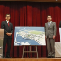 Shinji Inoue (second from right), the new minister overseeing the expo, reveals on Dec. 25 renderings of the venue that will host the event on Yumeshima island in the city of Osaka. | KYODO