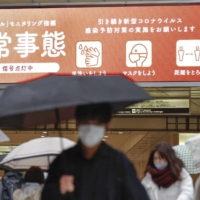 A notice in the center of Osaka on Tuesday advises the public that a state of emergency has been declared by prefectural authorities. | KYODO