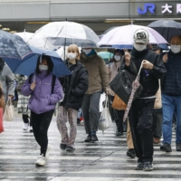 People walk in the rain Tuesday in the center of the city of Osaka. | KYODO