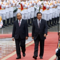 Cambodian Prime Minister Hun Sen (right) reviews an honor guard with his Vietnamese counterpart, Nguyen Xuan Phuc, in Hanoi, in October 2019.   |  REUTERS