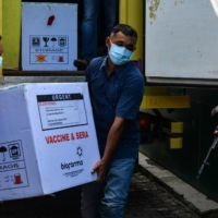 Workers unload Sinovac vaccines for COVID-19 from a truck at a warehouse in Banda Aceh, Indonesia, on Tuesday. | AFP-JIJI
