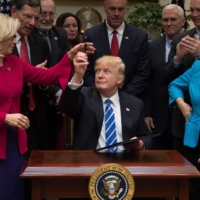 U.S. President Donald Trump gives a pen to House of Representatives lawmaker Liz Cheney during a signing ceremony in March 2017.  | AFP-JIJI