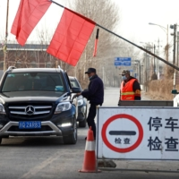 Volunteers stop a car at a checkpoint on the outskirts of Beijing amid a coronavirus outbreak on Tuesday.  | REUTERS