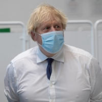 U.K. Prime Minister Boris Johnson visits a COVID-19 vaccination center in Bristol, England, on Monday.  | POOL / VIA REUTERS