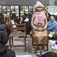 People sit around a statue of a girl symbolizing the issue of 'comfort women,' who suffered under Japan's military brothel system, in front of the Japanese Embassy in Seoul in December 2018. | KYODO