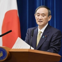 Prime Minister Yoshihide Suga speaks during a news conference Wednesday night at the Prime Minister's Office in Tokyo. | KYODO