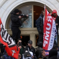 A man breaks a window as a mob of supporters of U.S. President Donald Trump storm the Capitol building in Washington on Jan. 6. | REUTERS