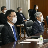 Bank of Japan Gov. Haruhiko Kuroda (second from left) attends the central bank's online meeting of branch managers on Thursday. | KYODO