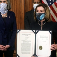 U.S. House Speaker Nancy Pelosi shows the article of impeachment against U.S. President Donald Trump after signing it in on Wednesday. Ten Republicans joined all the House Democrats in voting for the measure. | REUTERS
