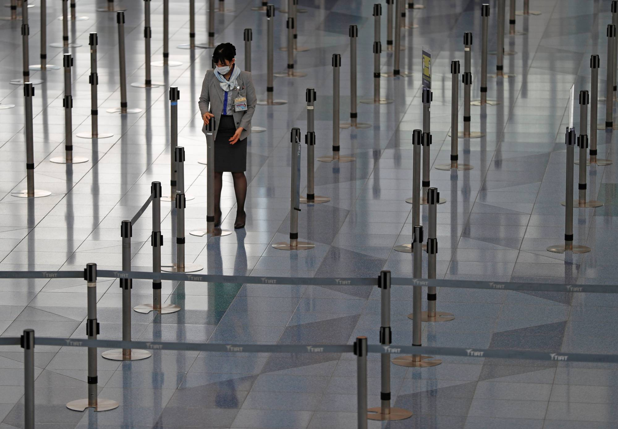 A staff member at an airline company works at the check-in area of the international flight terminal at Haneda Airport on Dec. 28 last year. | REUTERS