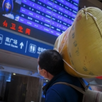 A traveler carries his belongings at a railway station in Beijing on Wednesday. | REUTERS