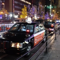 Taxis line up in Osaka's Dotonbori district in December. Taxi operators will be subject to the government's one-off cash benefits for companies hit by the COVID-19 pandemic, according to sources. | KYODO