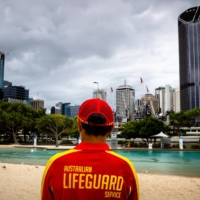 A lifeguard stands watch over a deserted South Bank beach on the first day of a snap lockdown in Brisbane on Jan. 9. Australia expects to approve the vaccine developed by Pfizer Inc. and BioNTech SE by the end of January and the AstraZeneca Plc vaccine next month, with shots also beginning in February. | AFP-JIJI