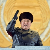 North Korean leader Kim Jong Un waves from a stage during a military parade celebrating a ruling Workers' Party of Korea congress in Pyongyang on Thursday. | KCNA / KNS / VIA AFP-JIJI