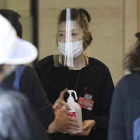 A Takashimaya department store employee brandishes hand sanitizer at the entrance of an outlet in Osaka in May. | KYODO