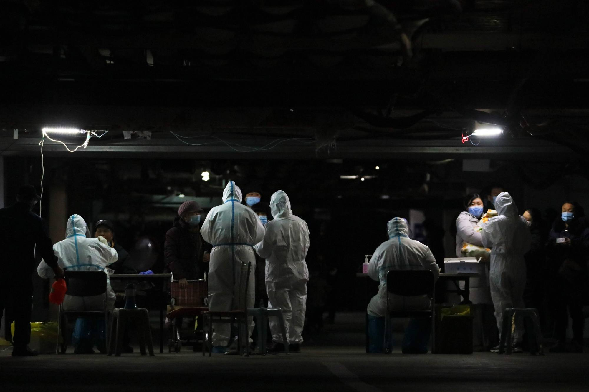 Residents undergo COVID-19 tests at the basement of a residential compound as part of a mass testing program following new cases of the virus emerging in Shijiazhuang in in central China's Hebei province.   | AFP-JIJI