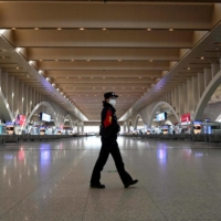 A police patrol officer walking at an empty railway station in Shijiazhaung, in northern China's Hebei province, on Jan. 7.  | AFP-JIJI