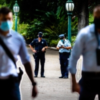 Queensland Police officers patrol the Brisbane Botanical Gardens on the first day of a snap lockdown in Brisbane on Saturday. | AFP-JIJI