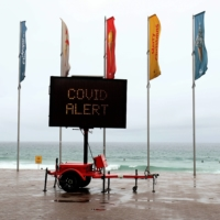 An electronic board displays a COVID-19 alert at a deserted Manly Beach in Sydney in December. | BLOOMBERG