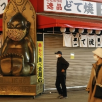 A restaurant in the Shinsekai district of Osaka is closed on Wednesday, with a sign posted saying it will remain closed until Feb. 7. | KYODO