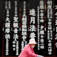 An elderly woman walks past a Buddhist temple in Tokyo's Asakusa neighborhood amid the COVID-19 outbreak in July. | REUTERS