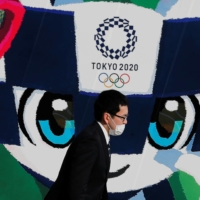 A man wearing a mask walks past a poster featuring Tokyo 2020 mascot Miraitowa in Tokyo on June 4, 2020.