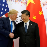 U.S. President Donald Trump shakes hands with Chinese leader Xi Jinping before starting their bilateral meeting during the Group of 20 leaders summit in Osaka in June 2019. | REUTERS