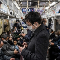 A train in Tokyo on Friday. The capital reported 2,001 COVID-19 cases on Friday and another 1,809 on Saturday.  | AFP-JIJI