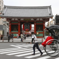A hand-pulled rickshaw in front of Kaminarimon (Thunder Gate), one of the gateways to the popular Sensoji temple in Tokyo's Asakusa district on Friday | KYODO