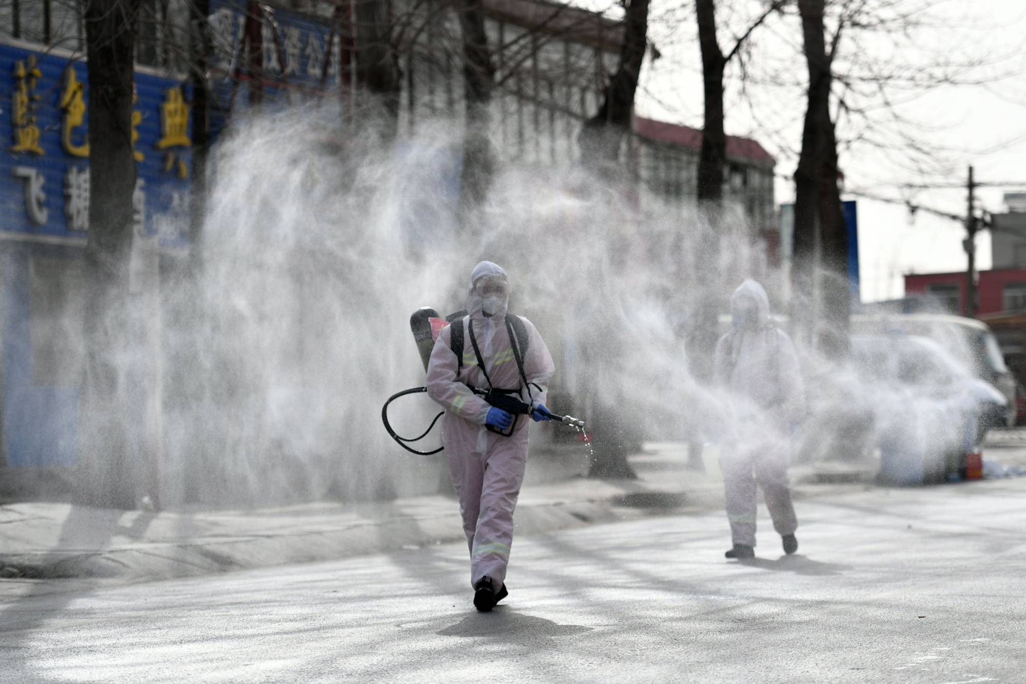 People spray disinfectant on a street in the Gaocheng district, which was declared a high-risk area for COVID-19, in Shijiazhuang in northern China's Hebei province. | AFP-JIJI