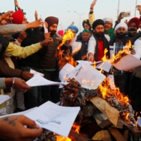Farmers burn copies of a law on agriculture that is target of mass protests at the Delhi-Uttar Pradesh border in Ghaziabad, India, on Wednesday.  | REUTERS