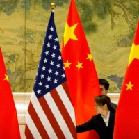 Chinese staffers adjust U.S. and Chinese flags before the opening session of Sino-U.S. trade negotiations in Beijing in February 2019. | POOL / VIA REUTERS