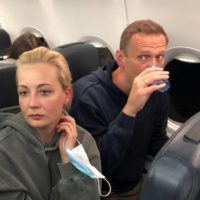 Russian opposition leader Alexei Navalny and his wife, Yulia Navalnaya, on their flight to Moscow on Sunday | REUTERS