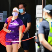 A tennis player and coach leave their hotel to train in Melbourne on Sunday. | AFP-JIJI