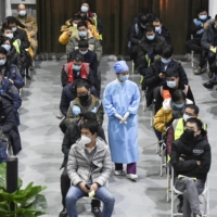 People wait to see if there are any reactions after receiving coronavirus vaccine shots in Beijing on Friday. | KYODO