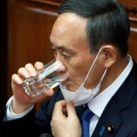 Prime Minister Yoshihide Suga takes a sip of water as he delivers his policy speech at the opening of the Lower House parliamentary session in Tokyo on Monday.   | REUTERS