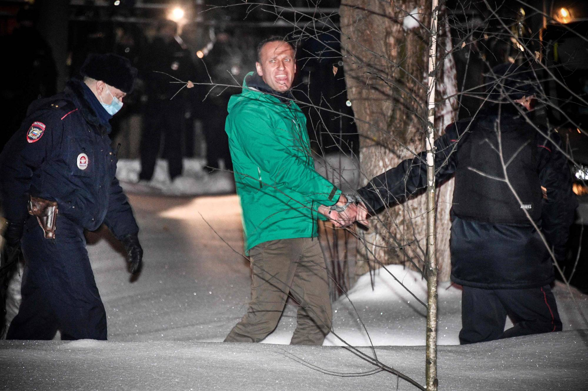 Opposition leader Alexei Navalny is escorted out of a police station in Khimki, outside Moscow, on Monday following a court ruling that ordered him jailed for 30 days.  | AFP-JIJI