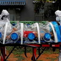 Paramedics prepare to transport a man showing symptoms of COVID-19 in Pretoria, South Africa, on Friday.  | AFP-JIJI