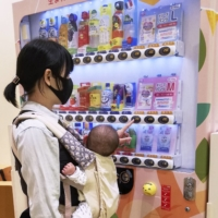 Some baby goods vending machines in Japan sell diapers and wet wipes alongside juices and other beverages. | COURTESY OF COMACHIPLUS / VIA KYODO