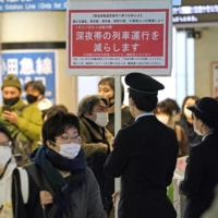 A JR East staff hold a sign that reads some late-night train services will be suspended at JR Shinjuku Station on Tuesday. | KYODO