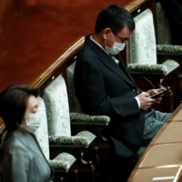Administrative and regulatory reform minister Taro Kono uses his smartphone next to Tokyo Olympics and Paralympic games Minister Seiko Hashimoto, before the opening of an ordinary session of the Diet in Tokyo on Monday. | REUTERS