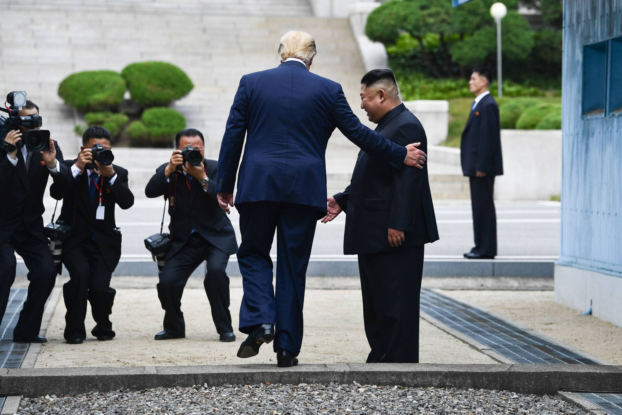 U.S. President Donald Trump steps into the northern side of the Military Demarcation Line that divides North and South Korea, as North Korean leader Kim Jong Un looks on, in the Joint Security Area of Panmunjom in the demilitarized zone, on June 30, 2019. | AFP-JIJI