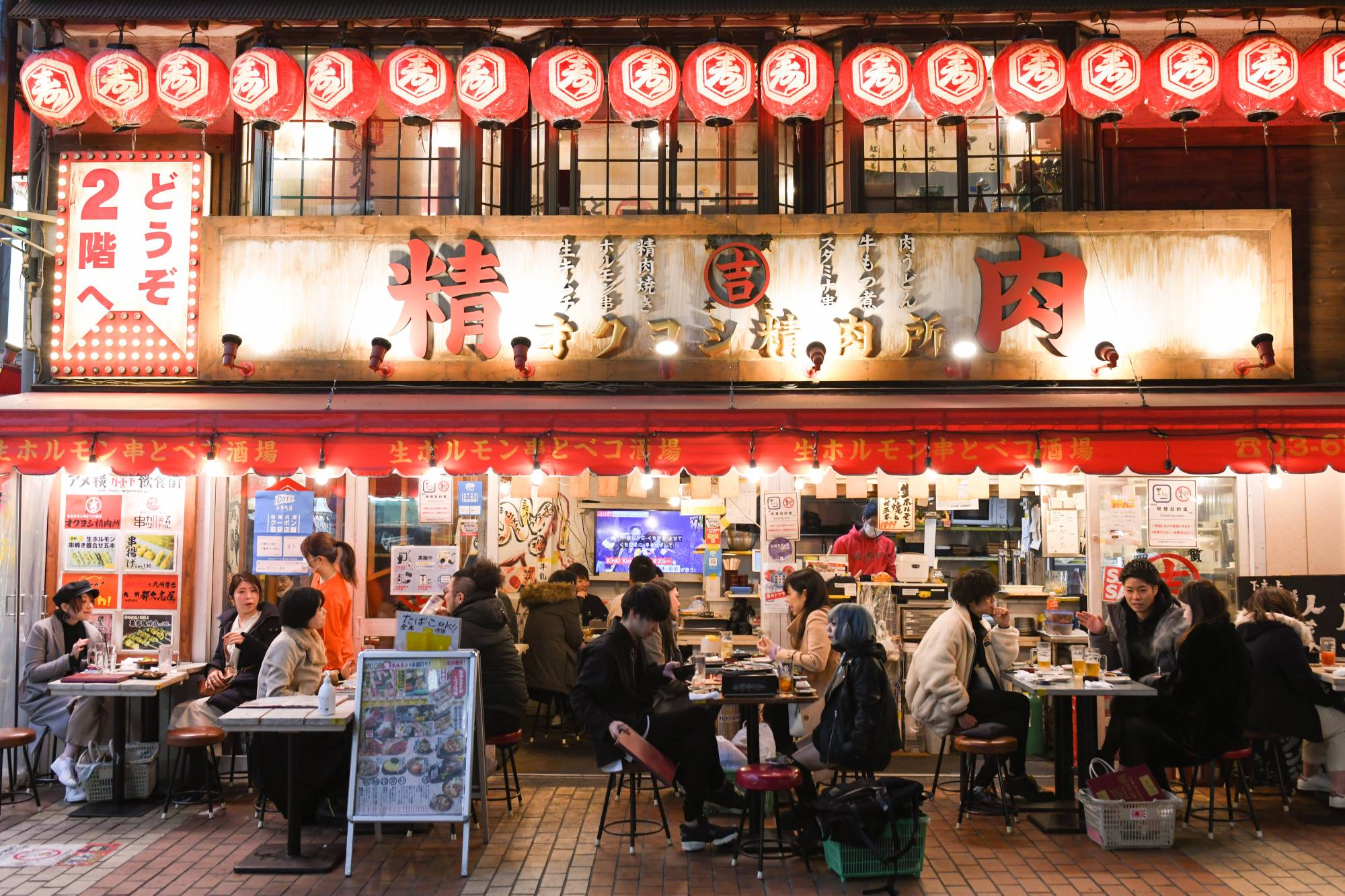 People dine at a restaurant at the Ameya Yokocho market in the Ueno district of Tokyo on Dec. 30. While many restaurants in Tokyo are following the requests in return for subsidies, others are starting to break ranks. | BLOOMBERG