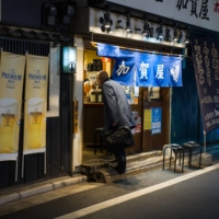 A customer walks into a restaurant in Tokyo on Jan. 8. | BLOOMBERG