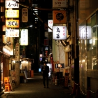 A man walks along a street before 8 p.m., the time the government asks restaurants and bars to close by, in Tokyo on Friday. | REUTERS