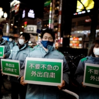 Staff members of the Tokyo Metropolitan Government hold placards during a march as they call for people to stay home and for restaurants and bars to shorten hours in Tokyo's Shinjuku district on Jan. 8. | REUTERS