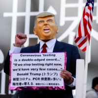 A man wearing a mask depicting U.S. President Donald Trump holds a placard in Toyko's Shibuya district on Jan. 9. | REUTERS