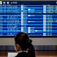 A staff member stands in front of a board displaying information on flight arrivals and cancellations at Tokyo's Haneda Airport on Dec. 27. | AFP-JIJI