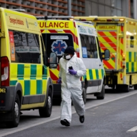 A medical delivery driver wearing PPE runs along a line of parked ambulances outside the Royal London hospital in London on Tuesday. An estimated 12% of people in England had been infected with the novel coronavirus by December last year, up from 9% in November, according to official antibody data released Tuesday. Health chiefs have warned intensive care units risk being overwhelmed by the surge in cases that has already led to the country suffering record numbers of daily deaths. | AFP-JIJI